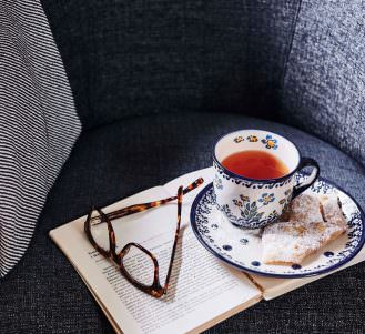 Close up photo of tea, dessert and book on sofa in library at Japara Hallam aged care home
