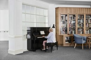 Elderly female resident playing piano at Japara Anglesea aged care home