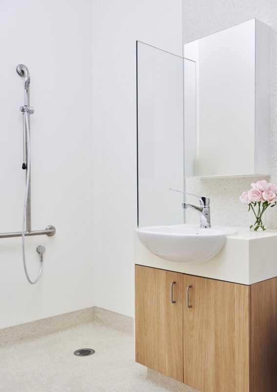 Wet room with wooden sink cabinet and pink flowers in vase