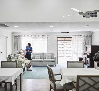 Dining room at Japara Noosa aged care home with elderly female resident and nurse