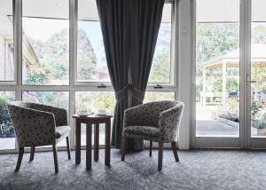 Lounge chairs and table with courtyard view at Japara Scottvale aged care home