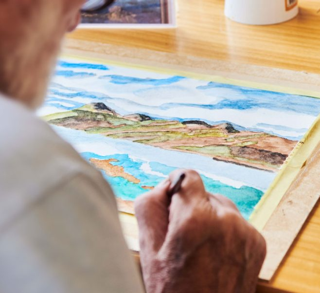 An older man paints watercolours at Japara Roccoco Aged Care Home