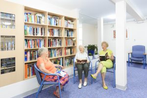 Three elderly residents reading at Japara Coffs Harbour aged care home