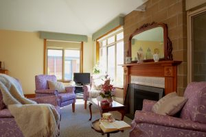 Living room with fireplace at Japara Kelaston aged care home