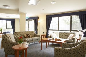 Living room with brown carpet at Japara Millward aged care home