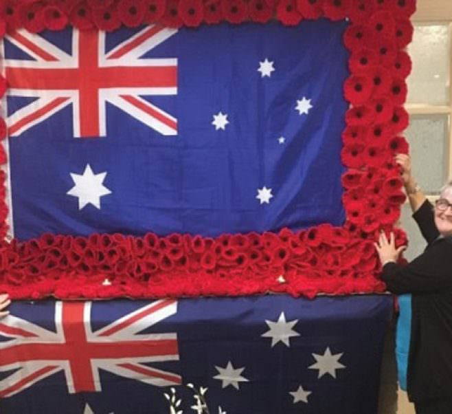 Lifestyle staff Julie Storie and Denise Johnston with the poppies and Australian Flags ahead of Remembrance Day.