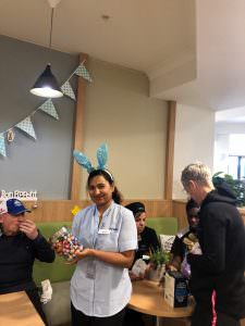 A st judes staff member wearing bunny ears holding a jar of Easter eggs