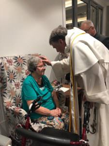 Archbishop Fisher performing a blessing on a resident