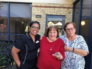 A japara st judes staff member standing next to two female residents eating chocolate