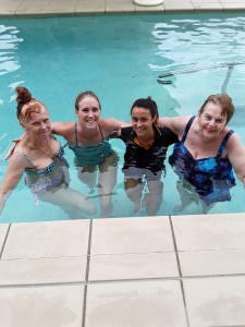 two staff members and two residents in the pool enjoying a swim