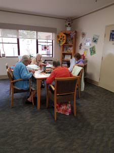 residents sitting around a table doing art activities