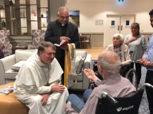 Archbishop Fisher speaking to a resident