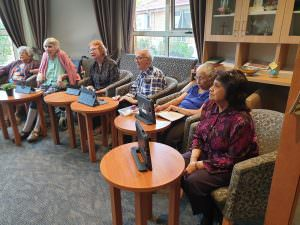 Residents learning how to use the tablet in front of them