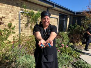 A Japara St Judes staff member holding a handful of little easter eggs