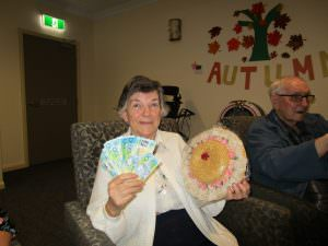 A resident posing for a photo with her prizes from the game of 'Two Up'