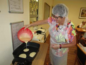 A volunteer at Albury & District making some pikelets