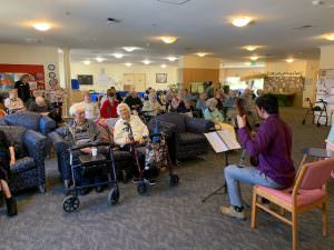 Dylan playing guitar for residents at The Homestead