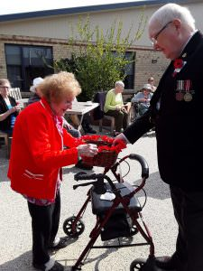 A member of the RSL hands a basket to a resident