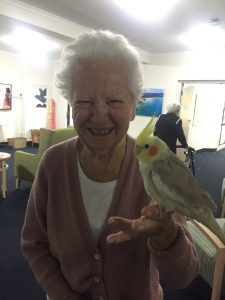 A smiling South West Rocks resident holding a bird on her arm