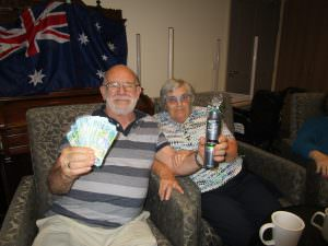 A couple residents posing for a photo with their prizes from the game of 'Two Up'