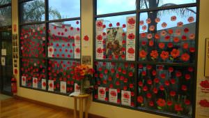 an array of poppys on the window of one of the Home's to symbolise Anzac day.