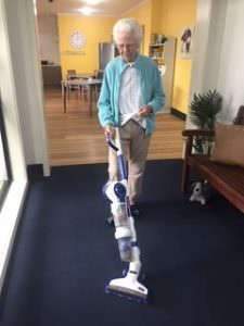 A South West Rocks resident vacuuming the carpet