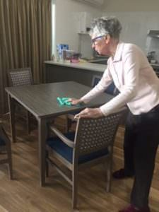 A South West Rocks resident wiping down a table