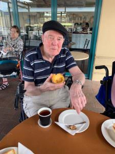 A resident enjoying a pastry and coffee at The Homestead