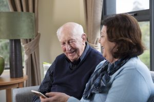 Woman and elderly man sitting together and looking at mobile phone