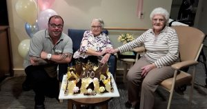 Man and two elderly ladies pose for a picture behind a large chocolate birthday cake