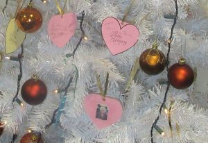 White Christmas tree with red and gold baubles, and pink heart-shaped messages from loved ones