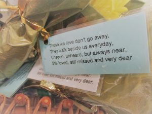 Blue labels attached to flower bouquet displaying a poem about remembering loved ones at Christmas