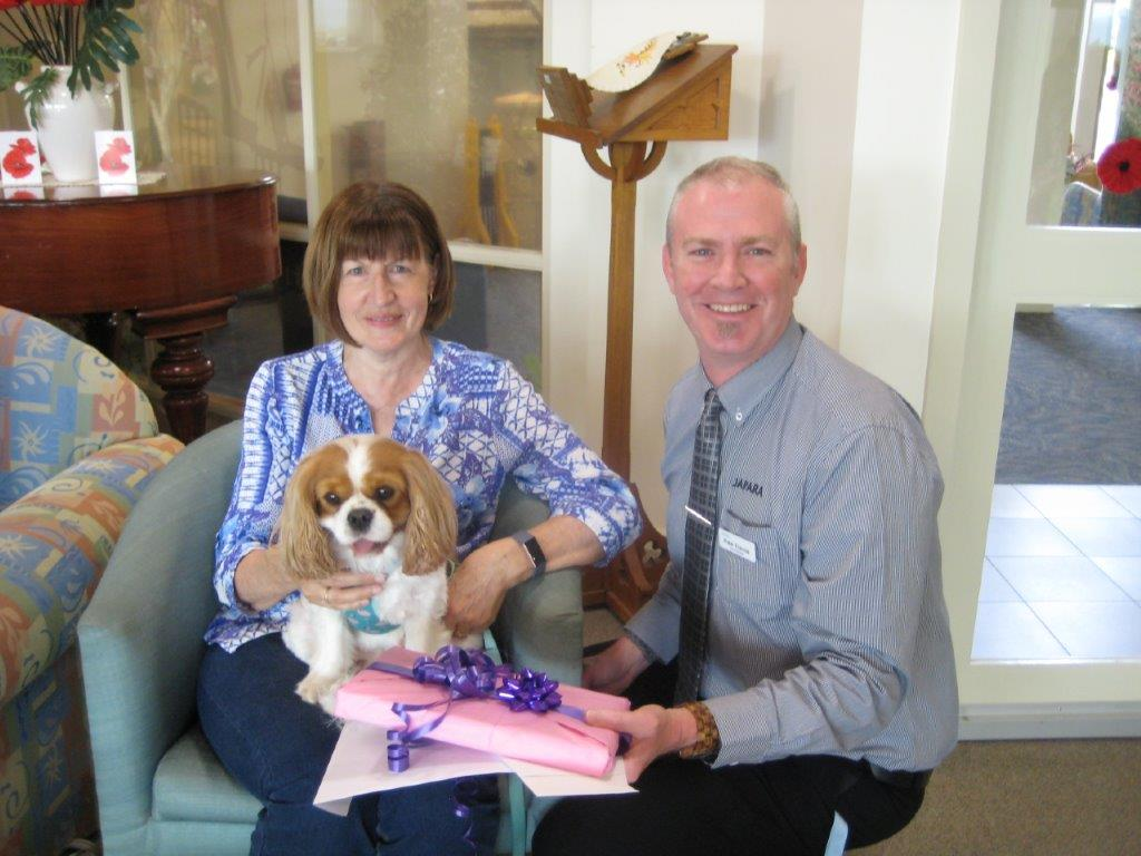Lily the therapy dog receiving a gift for her volunteer work at Japara Sandhill aged care home