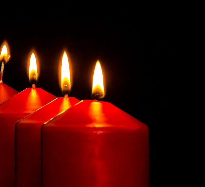 Three red candles lit against a black background