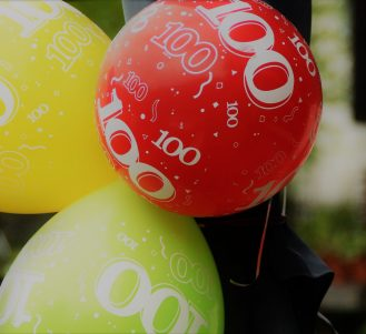 Yellow, red, and green 100th birthday balloons