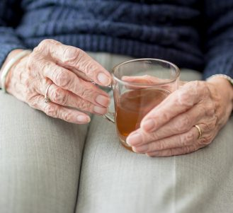 An elderly person's hand holding a glass of tea in her lap
