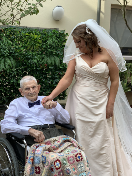 Woman in bridal dress holding the hand of a smiling, older man sitting in a wheelchair