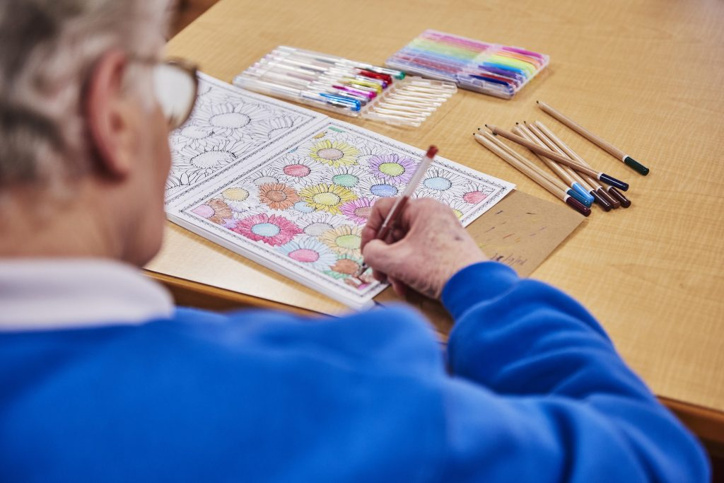 Elderly care home resident colouring in geometric shapes