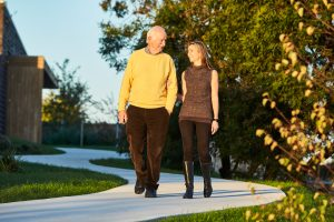 Elderly man and young woman walking down a path