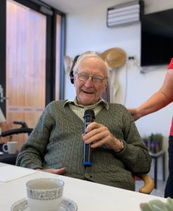 Elderly man laughing and holding microphone