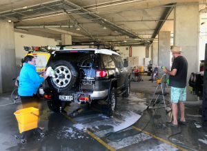 Two people washing a large car