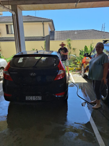 A man and a woman cleaning a car