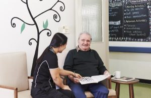 A smiling old man doing a crossword with a lady