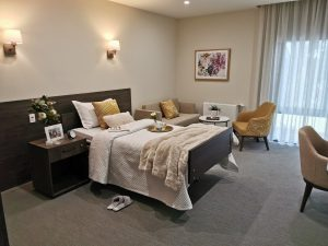 A large bedroom with a double bed, side table and living area