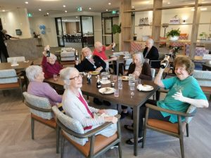 Smiling elderly residents sitting together in the living area with champagne