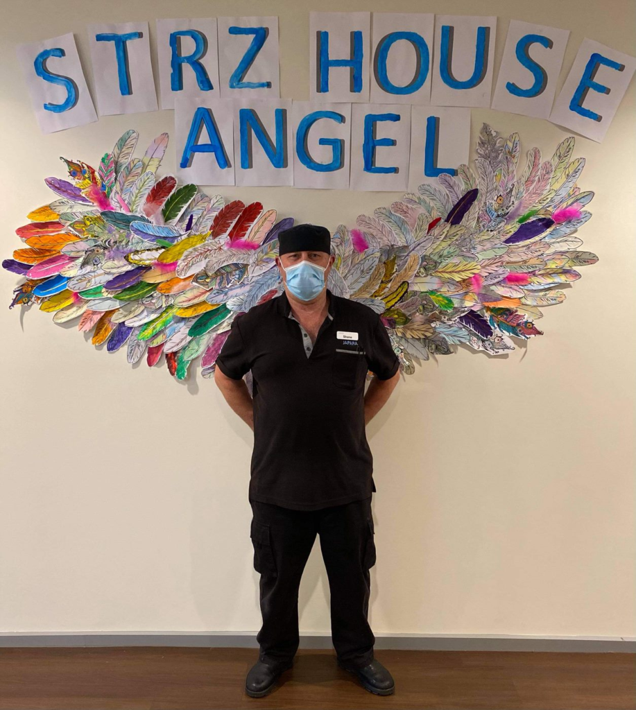 SMember of staff standing in front of the angel wings