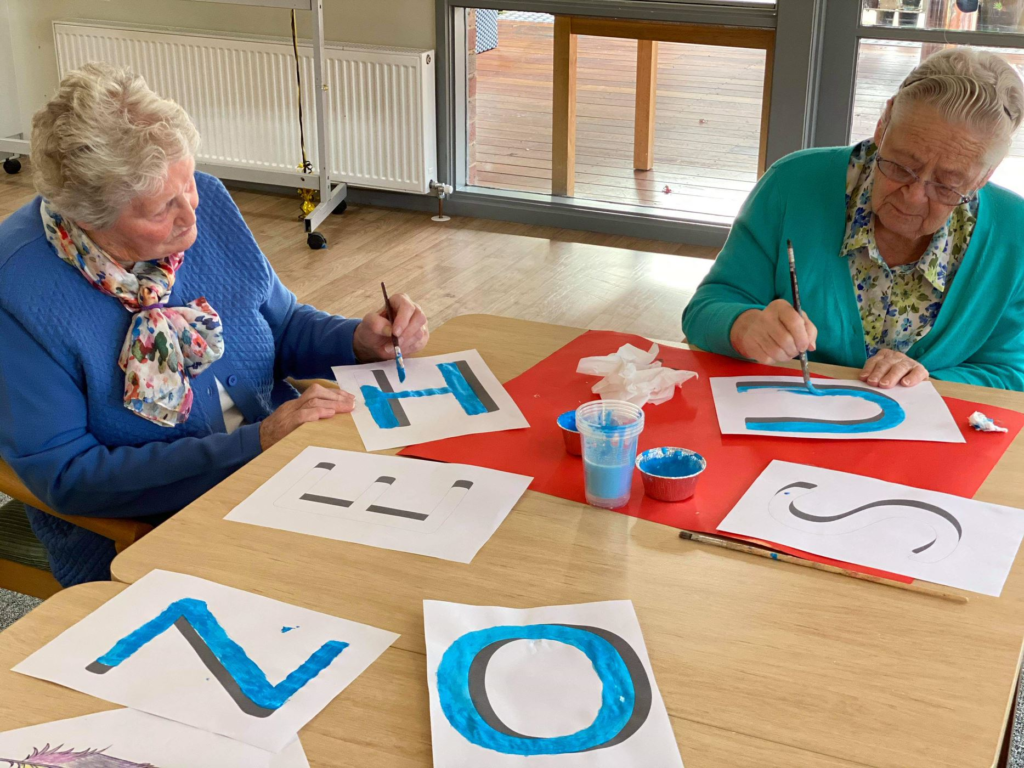 Two residents painting letters for the sign