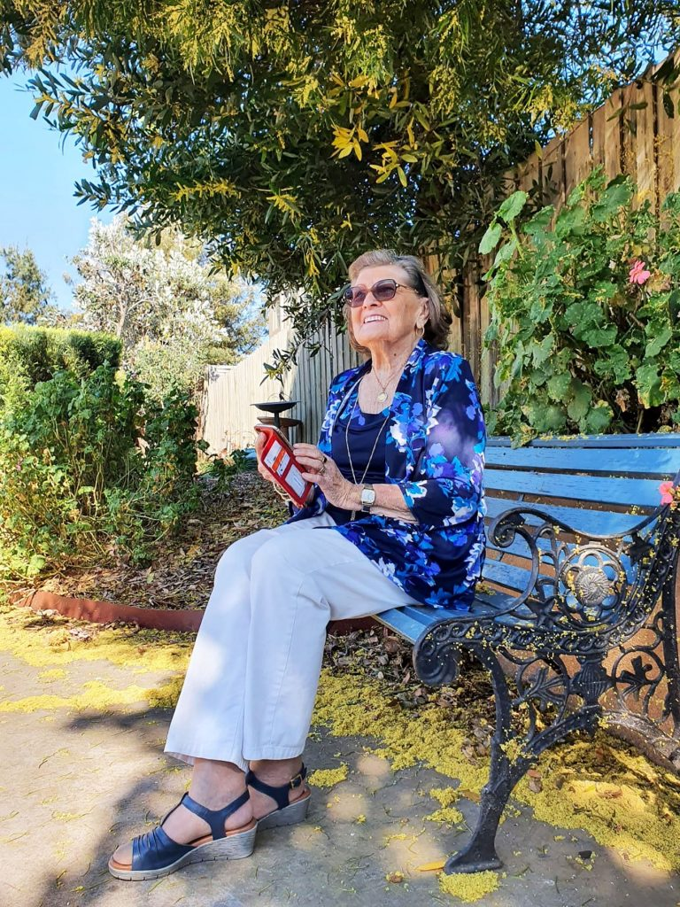 Elderly lady smiling and holding a red mobile phone sits on a blue park bench in a green garden