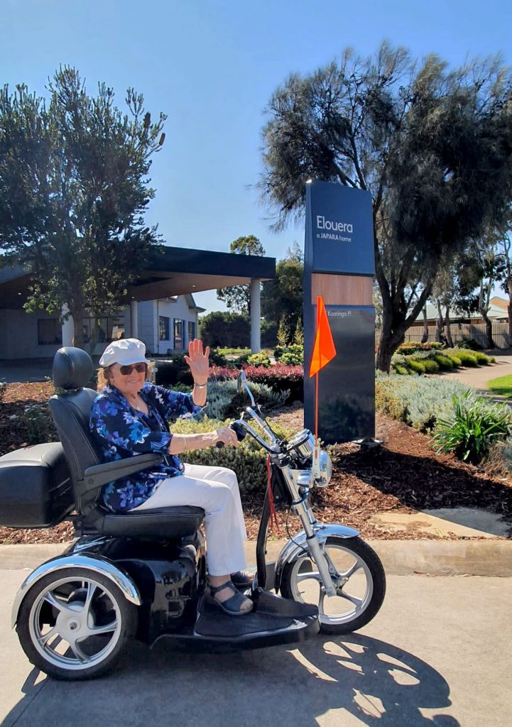 Elderly female lady riding her mobility scooter in the sun outside Elouera aged care home