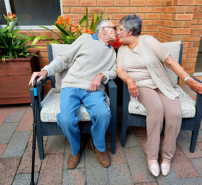 Elderly couple share a kiss on an outdoor bench